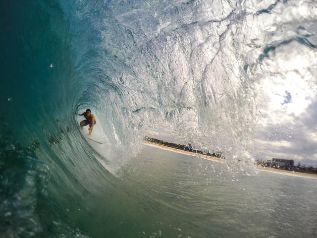 Surfer under a wave